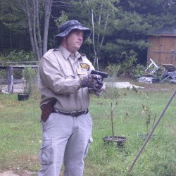 A man dressed as a law enforcement officer holds a pistol in a medical marijuana grower's backyard garden in Winterport, Maine, September 28, 2014, as seen in this surveillance image released by the Maine State Police.