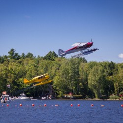 Two planes take off in unison during the spot landing competition at Saturday''s International Seaplane Fly-In on Moosehead Lake in Greenville.