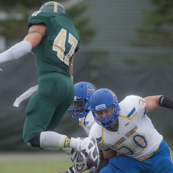 Husson University player Ellis Throckmorton (47) leaps to get past Alfred State lineman Matt Munson (30)  and quarterback Ben Wilkerson in the first half of their game in Bangor, Maine, Saturday, Sept. 20, 2014.