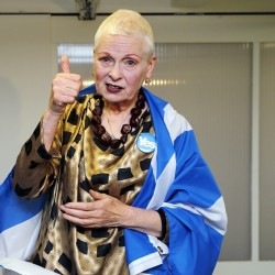 "Wearing a ""Yes"" badge and a Scottish flag in reference to Scotland's independence referendum, designer Vivienne Westwood gestures backstage before the presentation of her Spring/Summer 2015 collection during London Fashion Week."