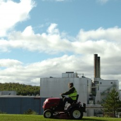 A town worker mows the Main Street median in front of the shuttered East Millinocket paper mill Sept. 16, 2011.