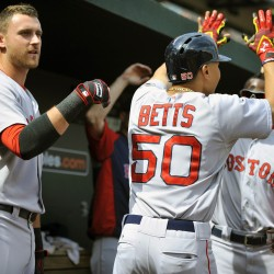 Boston's Mookie Betts (50) is congratulated by Will Middlebrooks and other teammates after hitting a solo home run in the first inning against the Baltimore Orioles at Oriole Park at Camden Yards in Baltimore Sunday.