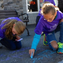 Fort Kent students Lacy Pelletier (left) and Gabrielle Martin create sidewalk art as part of the Chalk it Up Fort Kent domestic violence awareness event Friday.