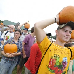Larry Crimi (foreground), 18, of Scranton, Pennsylvania, a conservation law enforcement major at Unity College, raises a locally grown organic pumpkin to the sky at the Common Ground Country Fair.