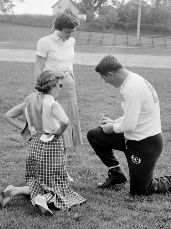 New York Giants halfback Alex Webster takes time out from an afternoon workout at Doyle Field in Brewer to sign autographs for two fans, Carol Stebbins (standing) and Charlotte Mulherin, both of Bangor, in 1959.