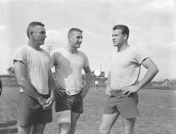 New York Giants halfback Frank Gifford (from right), rookie and former UM player Roger Ellis and quarterback Chuck Conerly discuss game plans at their practice session the day before the Giants played the Green Bay Packers in Bangor in September 1959.