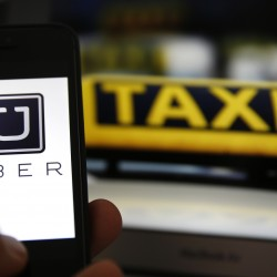 File illustration picture showing the logo of car-sharing service app Uber on a smartphone next to the picture of an official German taxi sign in Frankfurt, Sept. 15, 2014.