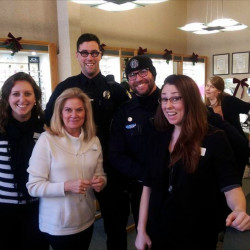 Portland Police Officers Graham Hults (left) and Joe Chappell pose for a photo with the staff at Casco Bay Eye Care earlier this month. The duo's temporary walking beat assignment ends this week.