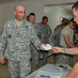First Sgt. Joseph Taylor of Bingham, Maine, picks up a letter during a recent mail call at the National Police Training Center in Paynesville, Liberia.
