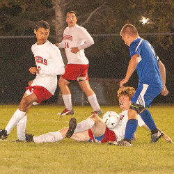 Fort Fairfield's Ryan Player (second from right) sits on the field with the ball on his stomach, while teammate Chris Gill (left) and Central Aroostook's Dustin Pryor (right) circle around him during the first half of their game Tuesday in Fort Fairfield. Fort Fairfield's Josh Ricker looks on from behind.