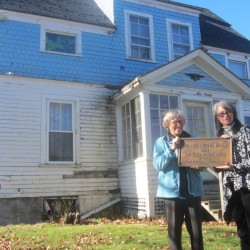 Rockland Historical Society curator Ann Morris (left) and real estate agent Michelle Gifford hold a bronze plaque that had marked this house on Broadway as the birthplace of poet Edna St. Vincent Millay on Nov. 9, 2015, in Rockland.