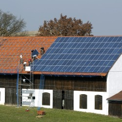 File photo of workers installing solar panels on the roof of a farmstead barn in Binsham near Landshut March 21, 2012.