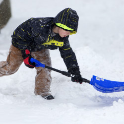 Kevan Royal, 8, helps shovel the driveway in Bangor, Jan. 16, 2016.