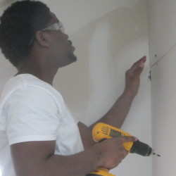 Tae Black attaches drywall to a third-floor room in a Brewster Street home in Rockland that is being completed by Habitat for Humanity volunteers.