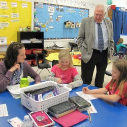 Educational technician Kathleen Cowperthwaite monitors a math station with students Chloe Skinner and Mylee Sylvia while Commissioner Bill Beardsley observes in Houlton on Dec. 22, 2015.