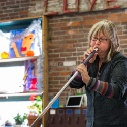 Linda Perrin puffs out her cheeks while blowing glass at her studio in Ellsworth on Tuesday.