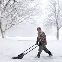 Jean-Paul Dugre shovels his driveway on Union Street in Bangor on Friday.