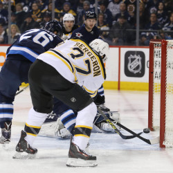 Boston Bruins center Patrice Bergeron (37) shoots the puck past Winnipeg Jets goalie Connor Hellebuyck (30) during the first period Thursdsay night at the MTS Centre in Winnipeg, Manitoba.
