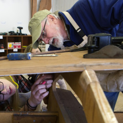 Rick Fitzsimmons (right) helps explain to Erin Kilpatrick, 16, how to properly mark where glue will go on the bottom of a boat during a class at the Penobscot Marine Museum's Hamilton Educational Center in Searsport recently. A group of retirees are working with students from Searsport District High School to build boats.