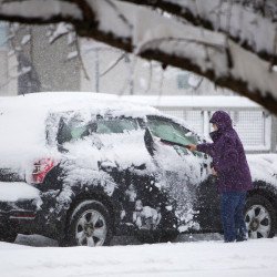 A woman clears her car of snow on Kenduskeag Plaza in Bangor on Feb. 5.