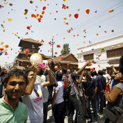 People release balloons during an event organized to commemorate the victims of last year's earthquakes in Kathmandu, Nepal, April 23, 2016.