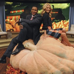 "Kelly Ripa and Michael Strahan sit on the ""World's Largest Pumpkin"", weighing at 1,872 pounds, during an appearance on ""LIVE with Kelly and Michael,"" on the set at WABC in New York, Oct. 16, 2012."