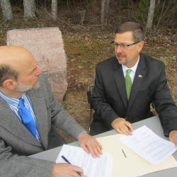 Stuart Swain, Interim President of University of Maine at Machias, left, and Joseph Cassidy, president of Washington County Community College, sign a collaborative agreement at the 45th Parallel in Perry.