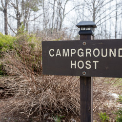 "A sign designates a campsite at Lamoine State Park for ""campground hosts."" The park provides sites for three volunteer hosts, according to park manager Charlene ""Sunshine"" Hood. In exchange for a free campsite at Lamoine State Park for the whole season, volunteer hosts will stack brush, patch the gravel roadways, help travelers set up their campsites, clean the shower-house, mow the grass, offer advice on local activities — pretty much whatever needs to be done. Unlike most sites, the ones in Lamoine include hookups for water and electricity."