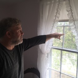 "James Pennell Lay points to the words ""Angel's Home"" etched in an upstairs bedroom window at 28 College St. in Brunswick. Lay's mother, Arline Pennell Lay, claims her grandfather, James Coffin, had the words from a song in the novel ""Uncle Tom's Cabin"" etched in the window of a room rented by Harriet Beecher Stowe in which she wrote the abolitionist novel."