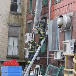 Firefighters work to put out a fire on Wednesday at the building housing Blaze restaurant in downtown Bangor.