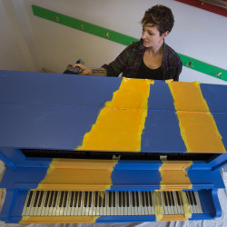 Andrea Beaulieu of Studio Linear paints a new street piano for downtown Bangor. For the sixth year in a row, Kid Central Festival will take place in downtown with new events to delight children and their families, including the unveiling of this new street piano.