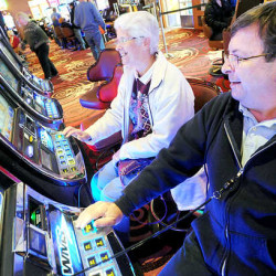 Chris Dispenzieri (left) of Bangor and Greg Hudak of Brewer play the slot machines at the Oxford Casino on Thanksgiving Day in 2013.