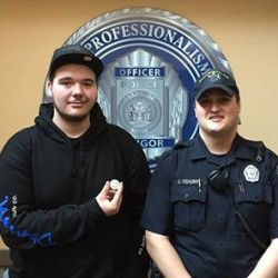John St. Germain III (left) accepts a Challenge Coin from Bangor police Officer Jose Vidaurri on Wednesday for his role in stopping a school bus allegedly stolen by a 12-year-old boy.