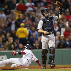 Boston Red Sox catcher Christian Vazquez (7) slides across home plate as Colorado Rockies catcher Dustin Garneau (13) catches a late throw during the second inning Tuesday night at Fenway Park in Boston.