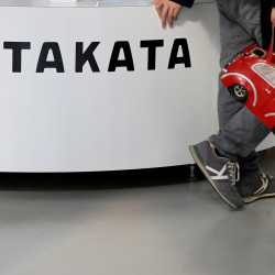 Visitors walk past a logo of Takata Corp on its display at a showroom for vehicles in Tokyo, Japan, in this February 2016 file photo.