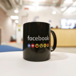 The Facebook logo and emoticons are seen on a coffee mug at the reception of its new office on Friday in Mumbai, India.