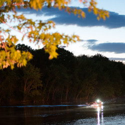 A boat searches the waters of the Stillwater River for a missing man on Tuesday evening near the parking lot of the University of Maine''s steam plant in Orono.