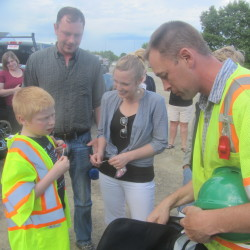Brian Farnham (left) receives gifts from Lane Construction project engineer T.J. Coyle (right) as the boy's parents, Colin (second from left) and Heather Nelson, watch on Thursday in Rockland.