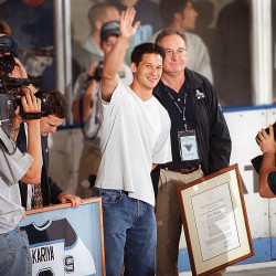 Paul Kariya, flanked by University of Maine President Peter Hoff, waves to hockey fans after his No. 9 jersey was retired by the school during a ceremony in July 2001 at Alfond Arena.