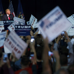 Supporters of presumptive Republican presidential nominee Donald Trump hold up signs as Trump speaks during a campaign rally on Wednesday at the Cross Insurance Center in Bangor.