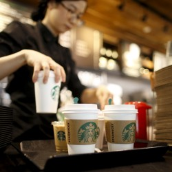 A staff serves beverages at a Starbucks coffee shop, March 7, 2016