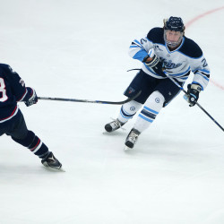 The University of Maine's Dan Renouf (right) moves the puck past the University of Connecticut's Joey Ferriss during their hockey game on Jan. 16 at Alfond Arena in Orono.