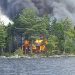 A fire that smoldered for hours destroyed an unoccupied camp building on Thursday on an island in North Twin Lake.