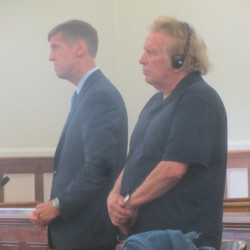 Don McLean (right) pleaded guilty to a series of domestic violence offenses Thursday in Knox County Unified Court in Rockland. McLean wore headphones to help him hear the proceedings. His lawyer Walter McKee stands next to him.
