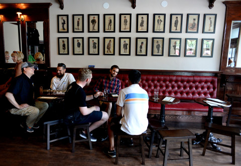 People chat in Gary and Sharon Cresswell's newly opened Airline Brewing Co., a British-style pub decorated with more that 30 original Vanity Fair illustrations from the late 1800s, on July 15 in Ellsworth.