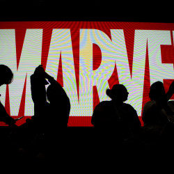 Attendees sit in front of an illuminated Marvel sign during the second day of Comic-Con 2016, July 21, 2016 in San Diego.