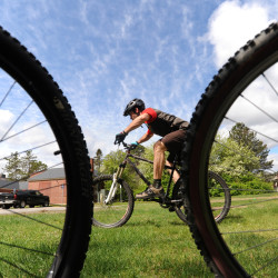 Michael Smith, program director and chief operating officer with the Maine Winter Sports Center, demonstrates basic mountain biking skills in this May 2015 file photo. The Maine Winter Sports Center is being renamed as the Outdoor Sport Institute.