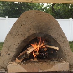 A fire burns inside a clay oven during Stu Silverstein's oven-making workshop on Thursday at the 10th annual Kneading Conference in Skowhegan.