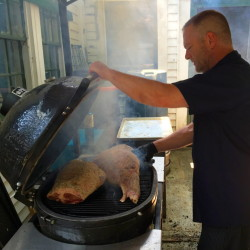 Dirk Yeaton, head chef at Pig + Poet, cooks legs of lamb on his smoker on July 21 at Whitehall in Camden.
