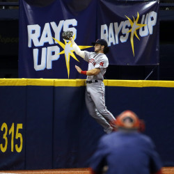 Boston Red Sox left fielder Andrew Benintendi (40) falls into the wall as he catches the ball during the eighth inning against the Tampa Bay Rays Monday night at Tropicana Field in St. Petersburg, Florida.